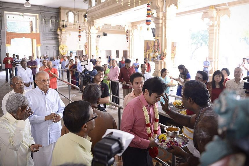 MCCY Minister Lawrence Wong (centre) is blessed by assistant priest Suresh Kannan in front of the main sanctum at Sri Thendayuthapani Temple after the official ceremony to gazette it as a national monument on Oct 20,2014.-- ST PHOTO: MARK