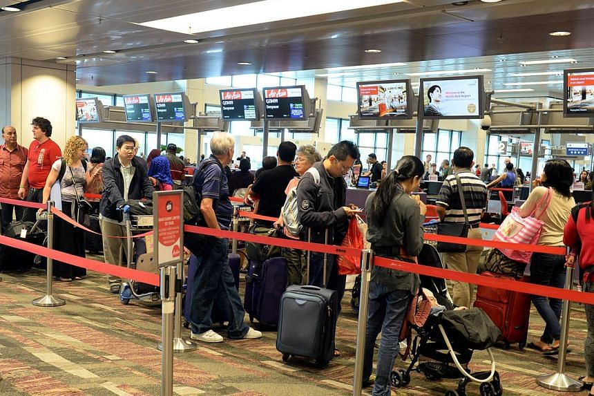 Passengers waiting to check in at the AirAsia counter at Changi Airport Terminal 1. -- PHOTO: ST FILE