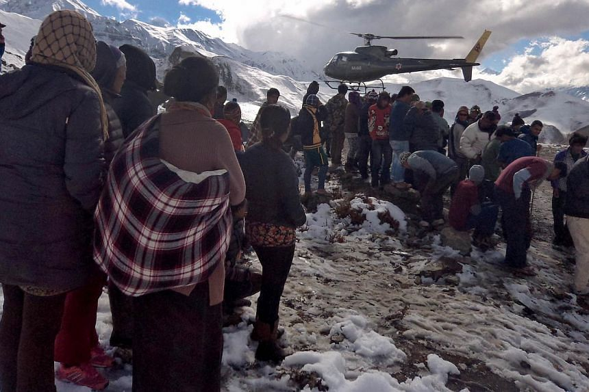In this handout photograph released by the Nepal Army on Oct 15, 2014, a Nepalese Army helicopter rescues survivors of a snow storm in Manang District, along the Annapurna Circuit Trek. -- PHOTO: AFP