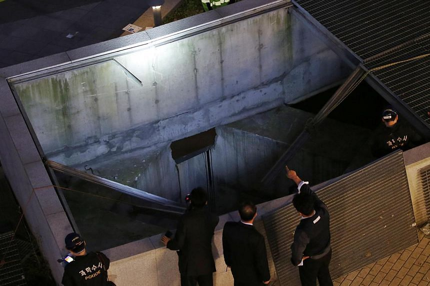 Police officials examine the scene of an accident at a shopping district in Seongnam on Oct 17, 2014. -- PHOTO: AFP