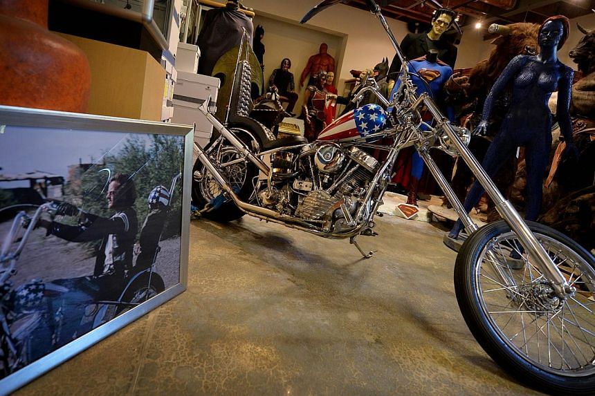 "The iconic Harley-Davidson chopper ridden by Peter Fonda (in photo on left) in the 1969 classic ""Easy Rider"" prior to it's auction at Calabasas, California on Sept 18, 2014. -- PHOTO: AFP"