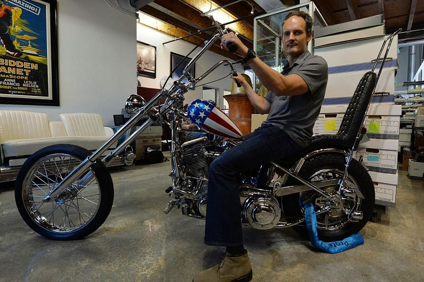 Auctioneer Brian Chanes with the iconic Harley-Davidson chopper riden by Peter Fonda in the 1969 classic Easy Rider prior to its auction at Calabasas, California on Sept 18, 2014. -- PHOTO: AFP