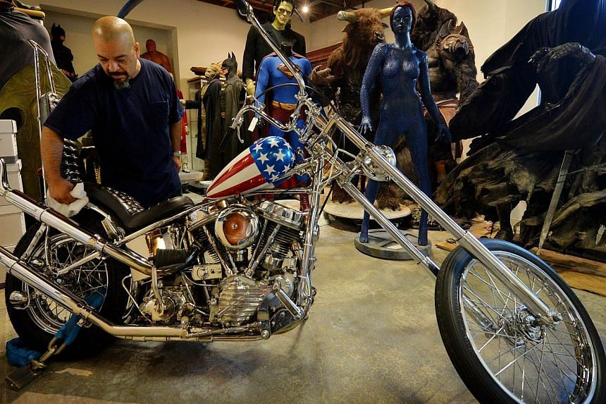 A worker cleans the iconic Harley-Davidson chopper ridden by Peter Fonda (in photo on left) in the 1969 classic Easy Rider prior to its auction at Calabasas, California on Sept 18, 2014. -- PHOTO: AFP