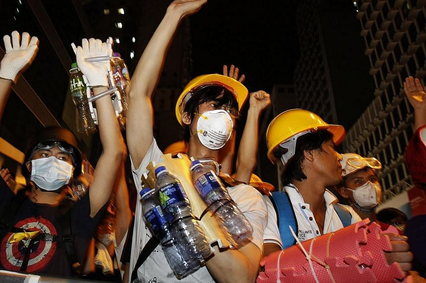 Pro-democracy protesters, protecting themselves with helmets, masks, foam pads and empty plastic bottles, raise their hands at riot police as a gesture of peace after they were told by visiting lawmakers not to charge the police defence line, at Mong