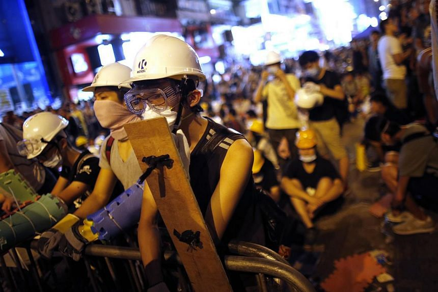 Pro-democracy protesters stand by a barricade as they prepare for a confrontation with riot police at the Mongkok shopping district of Hong Kong on Oct 19, 2014. -- PHOTO: REUTERS