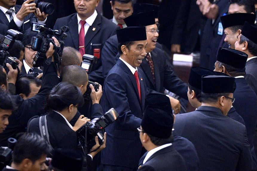 Newly appointed Indonesian President Joko Widodo (middle) being congratulated after his inauguration. -- ST PHOTO: LIM SIN TAI