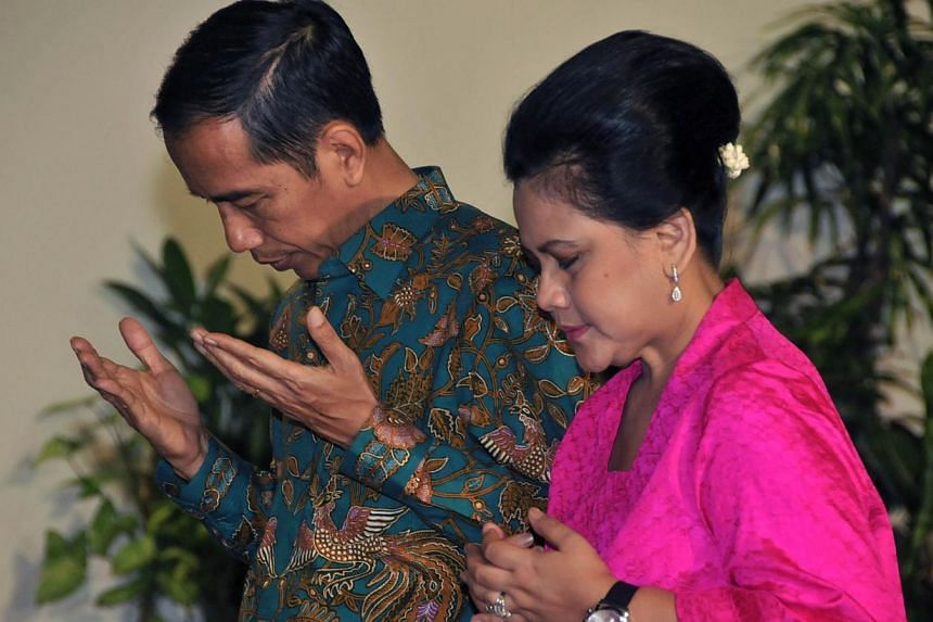Mr Joko Widodo together with his wife Iriana Widodo pray during an open house reception for hundreds of Solo city residents at Solo city hall in Central Java province on July 30, 2014. -- PHOTO: AFP