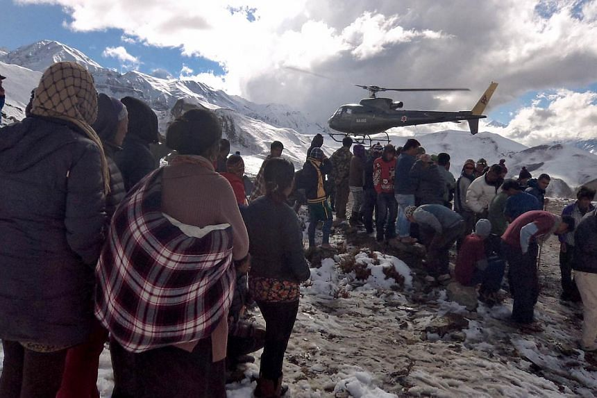 Nepalese Army helicopter rescues survivors of a snow storm in Manang District, along the Annapurna Circuit Trek. -- PHOTO: AFP