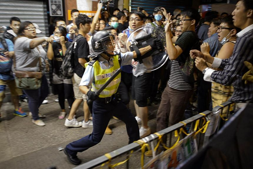 A policeman holding a baton advances towards pro-democracy protesters as they clash on a street in the Mong Kok district of Hong Kong early on Oct 19, 2014. -- PHOTO: AFP