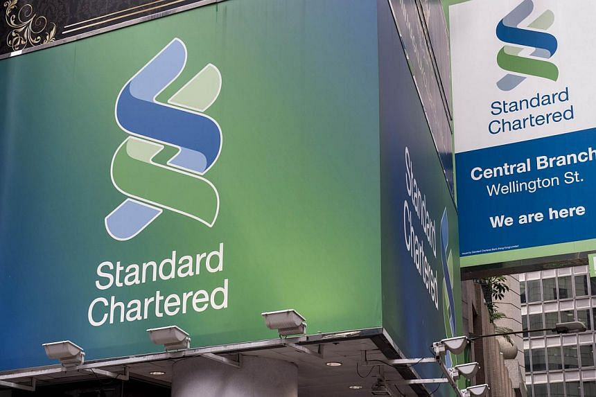 This Aug 6, 2014 file photo shows Standard Chartered billboards as they hang above a bank branch in Hong Kong. -- PHOTO: AFP