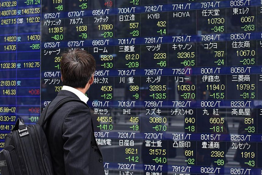 A pedestrian watches a share prices board displayed on a window of a securities firm in Tokyo on Oct 16, 2014. -- PHOTO: AFP