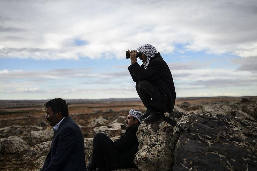 Kurdish people watch the Syrian town of Ain al-Arab, known as Kobane by the Kurds, from the Turkish border in the south-eastern village of Mursitpinar, Sanliurfa province on Oct 19, 2014. -- PHOTO: AFP