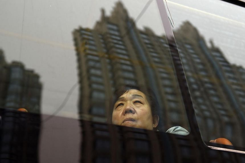 Residential buildings are reflected in a bus window as a passenger looks out, in Beijing on Sept 28, 2014. With a faltering property market increasingly dragging on manufacturing and investment, growth in the world's second-largest economy cooled to