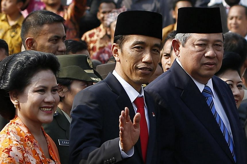 Indonesia's new President Joko Widodo (centre) with his wife Iriana Joko Widodo wave next to former president Susilo Bambang Yudhoyono at the presidential palace in Jakarta, Oct 20, 2014. -- PHOTO: REUTERS