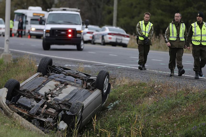 A Surete du Quebec officer investigates an overturned vehicle in Saint-Jean-sur-Richelieu, Quebec, on October 20, 2014. Two Canadian soldiers were injured in a hit-and-run on Monday by a male driver who was later shot dead by police officers. -- PHOT