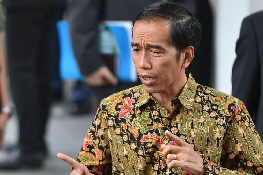 Indonesian President Joko Widodo answers journalists' questions outside the Palace in Jakarta on Oct 21, 2014 during his first day as President after his inauguration on Oct 20, 2014. -- PHOTO: AFP
