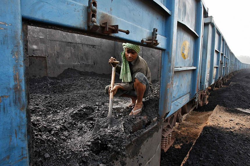 A worker unloads coal from a goods train at a railway yard in the northern Indian city of Chandigarh in this July 8, 2014, file photo.-- PHOTO: REUTERS