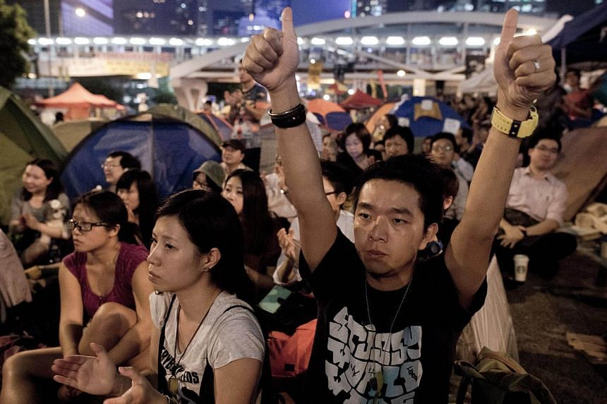 Pro-democracy demonstrators react as they watch a live transmission on a giant screen of talks with leaders of the Hong Kong Federation of Students and Hong Kong authorities, in the Admiralty district of Hong Kong on Oct 21, 2014. -- PHOTO: AFP