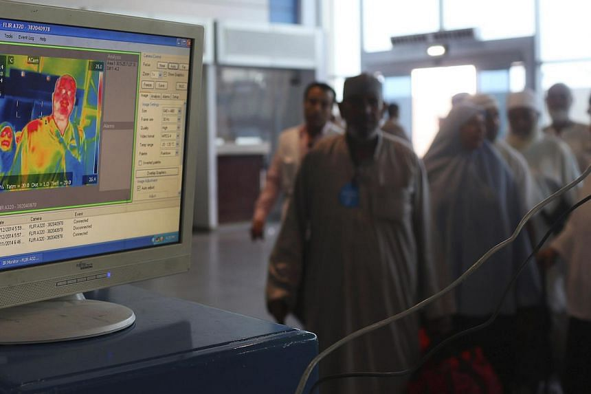 Health workers use an infrared scanner to scan the temperatures of passengers returning from haj pilgrimage in Saudi Arabia, at Cairo Airport on Oct 13, 2014.A new device similar to a simple pregnancy home-test could allow doctors to diagnose a