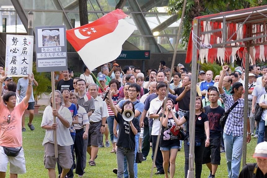 Han Hui Hui (with loudspeaker) and Roy Ngerng (carrying state flag) with supporters at the Return Our CPF rally, marching round the park at the conclusion of the rallyon Sept 27, 2014.Local blogger Han Hui Hui will not be allowed to