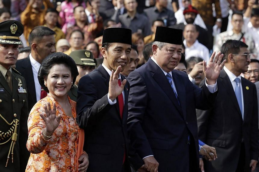 Indonesian President Joko Widodo (third left), with First Lady Iriana Widodo (second left), is accompanied by outgoing president Susilo Bambang Yudhoyono (fouth left) at the Presidential Palace in Jakarta during the official welcome ceremony on Oct 2