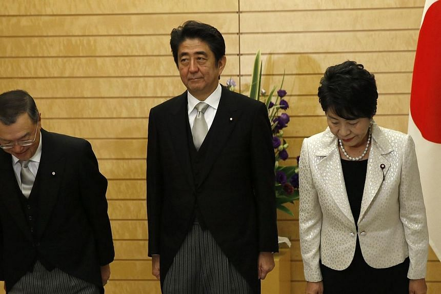Japan's Prime Minister Shinzo Abe (centre) poses for the media with new Economy, Trade and Industry Minister Yoichi Miyazawa (left) and new Justice Minister Yoko Kamikawa at Abe's official residence in Tokyo on Oct 21, 2014. Mr Abe is facing inc