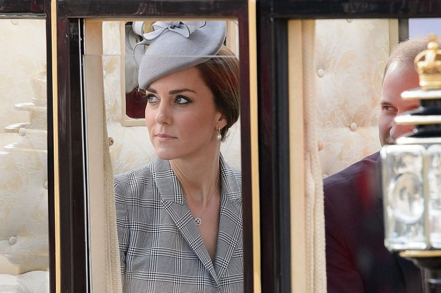 Britain's Catherine, Duchess of Cambridge (left), takes her seat in a State Carriage with her husband Britain's Prince William, Duke of Cambridge (right), for the carriage procession to Buckingham Palace as part of the ceremonial welcome ceremony for