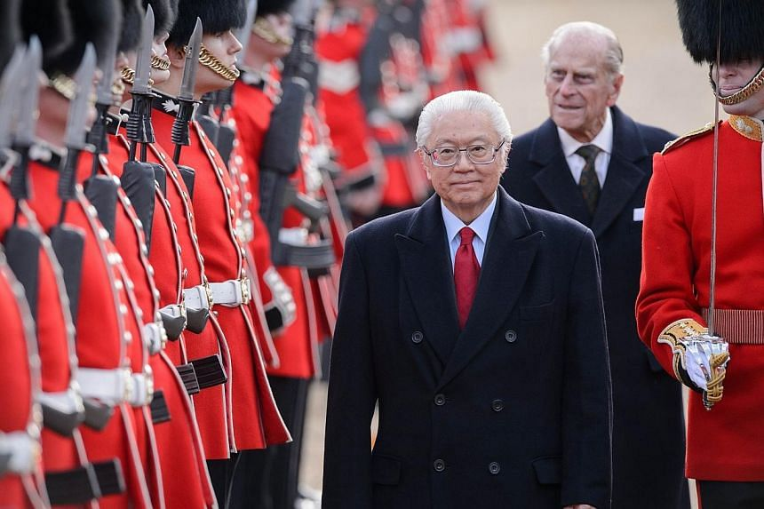 Singapore's President Tony Tan Keng Yam (centre) reviews an honour guard accompanied by Britain's Prince Philip, Duke of Edinburgh (back, second right) during the ceremonial welcome ceremony for the Singaporean president at the start of a state visit