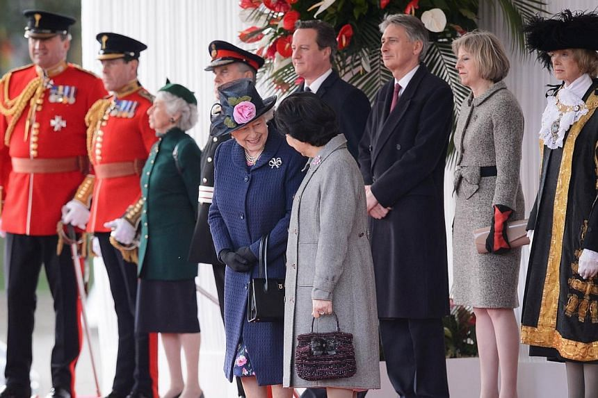 Britain's Queen Elizabeth II (front left) talks with Mary Tan (front right), wife of Singapore's President Tony Tan Keng Yam, as British Prime Minister David Cameron (back fourth right), Foreign Secretary Philip Hammond (back third right)and Home Sec