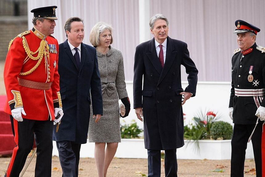 British Prime Minister David Cameron (second left), Home Secretary Theresa May (centre) and Foreign Secretary Philip Hammond (second right) arrive to attend the ceremonial welcome ceremony for Singapore's President Tony Tan Keng Yam at the start of a