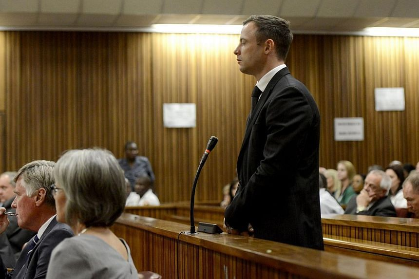 Paralympian Oscar Pistorius stands in the dock as judgment is delivered at the high court in Pretoria on Oct 21, 2014. -- PHOTO: AFP