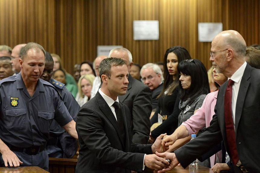 Paralympian Oscar Pistorius holds the hands of his uncle Arnold as he is taken down to the holding cells after being sentenced to five years imprisonment for the culpable homicide killing of his girlfriend Reeva Steenkamp at the high court in Pretori