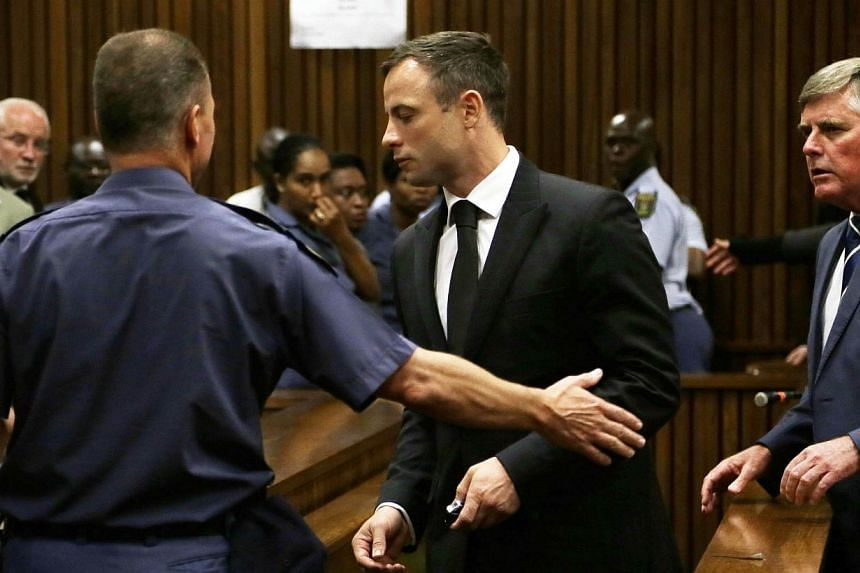 South African Paralympic athlete Oscar Pistorius is lead by officer into a holding cell after being sentenced at the high court in Pretoria on Oct 21, 2014. -- PHOTO: AFP
