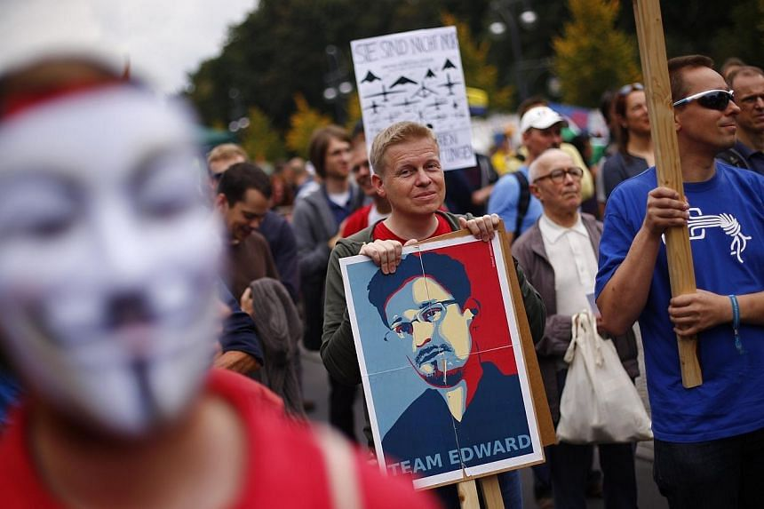 "A man holds a placard with a portrait of former US National Security Agency contractor Edward Snowden during a ""Freiheit Statt Angst"" (Freedom instead of Fear) protest calling for the protection of digital data privacy and the reigning in of digital"
