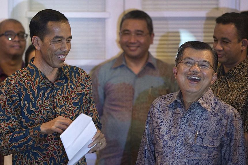 Indonesia's president-elect Joko Widodo (left) and his vice president-elect Jusuf Kalla laugh while speaking to the media at their transition headquarters in Jakarta on Sept 15, 2014. -- PHOTO: REUTERS
