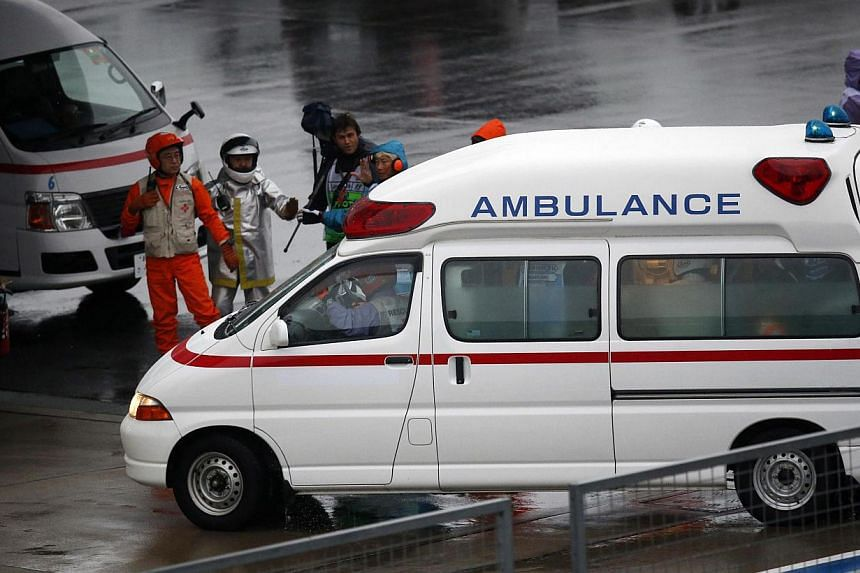 Marshalls clear the way for an ambulance after the race was stopped following a crash by Marussia Formula One driver Jules Bianchi of France at the Japanese F1 Grand Prix at the Suzuka Circuit on Oct 5, 2014. -- PHOTO: REUTERS