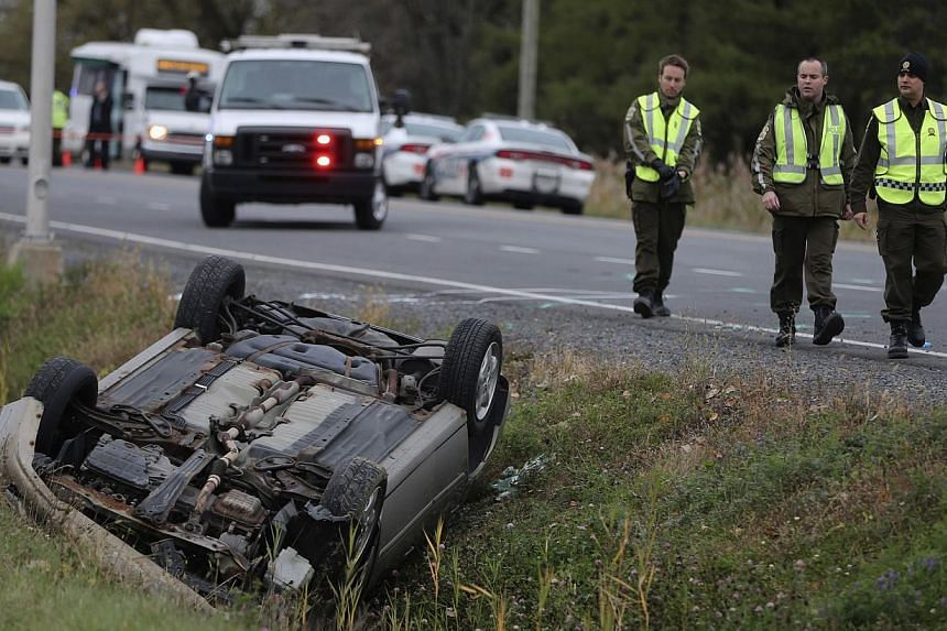 A Surete du Quebec (SQ) officer investigates an overturned vehicle in Saint-Jean-sur-Richelieu, Quebec on Oct 20, 2014. One of two Canadian soldiers run down by a car driven by a suspected Islamic State militant has died, police said on Tuesday,