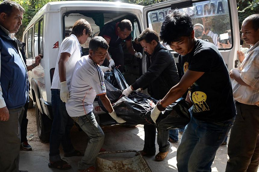 Volunteers shift the recovered body of a trekker killed in a snowstorm and an avalanche on Nepal's Annapurna Circuit, at the Teaching Hospital morgue in Kathmandu on Oct 20, 2014. -- PHOTO: AFP