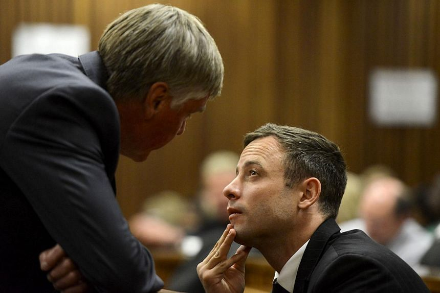 South African Paralympic athlete Oscar Pistorius (right) listens to one of the members of his legal team at the High Court in Pretoria on Oct 21, 2014. -- PHOTO: AFP