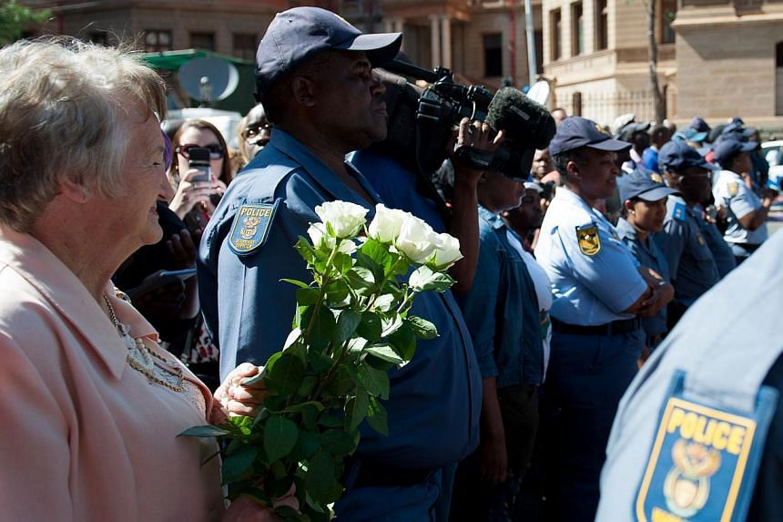 A supporter of South African Paralympic athlete Oscar Pistorius hold flowers as she waits outside the High Court in Pretoria on Oct 21, 2014. -- PHOTO: AFP