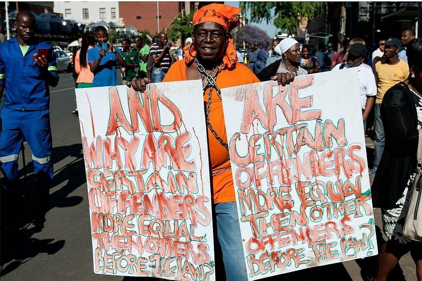 A man holds signs protesting outside the High Court in Pretoria before South African Paralympic athlete Oscar Pistorius arrived at court on Oct 21, 2014. -- PHOTO: AFP