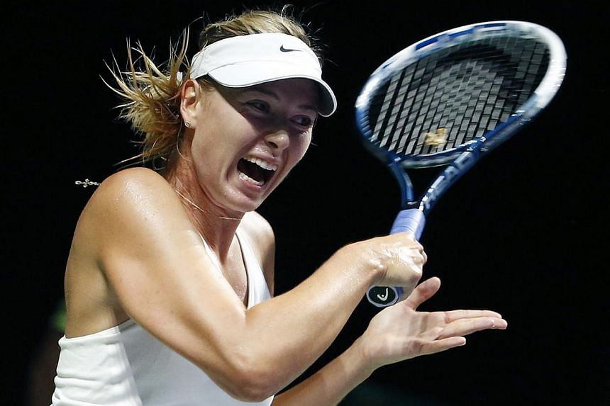 Maria Sharapova of Russia plays a shot against Caroline Wozniacki of Denmark during their WTA Finals singles tennis match at the Singapore Indoor Stadium Oct 21, 2014. -- PHOTO: REUTERS