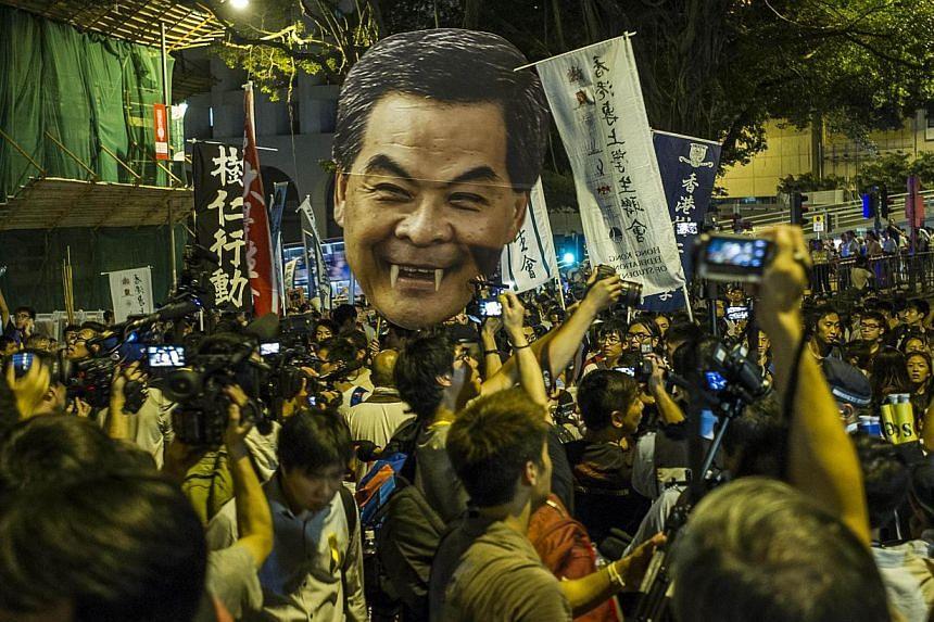 Students march to the Government House in Hong Kong holding a portrait of Chief Executive Leung Chun Ying, on Sept 25, 2014. -- PHOTO: AFP