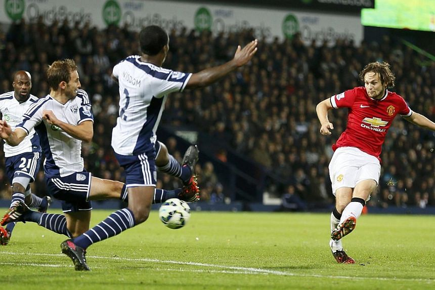 Daley Blind of Manchester United (right) shoots to score against West Bromwich Albion during their English Premier League match at The Hawthorns in West Bromwich on Oct 20, 2014. -- PHOTO: REUTERS