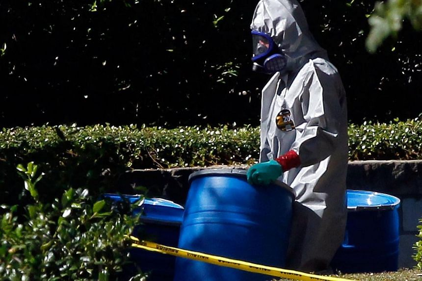 A hazmat worker removes a barrel from The Village Bend East apartment where a second healthcare worker who has tested positive for the Ebola virus resides in Dallas, Texas on Oct 16, 2014. -- PHOTO: AFP