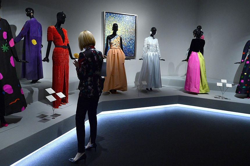 """A woman looks at creations displayed at the exhibition titled """"Hubert de Givenchy"""" at the Thyssen-Bornemisza museum in Madrid on Oct 20, 2014. -- PHOTO: AFP"""