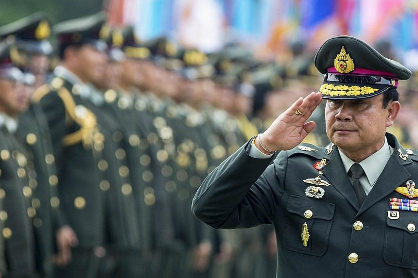 Thailand's Prime Minister Prayuth Chan-ocha salutes members of the Royal Thai Army after a handover ceremony for the new Royal Thai Army Chief, General Udomdej Sitabutr, at the Thai Army Headquarters in Bangkok on Sept 30, 2014. A council select