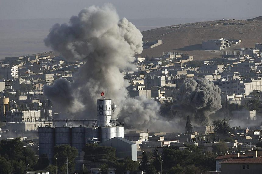 Smoke rises after an US-led air strike in the Syrian town of Kobani Oct 10, 2014. ISIS militants were producing about US$2 million (S$2.54 million) worth of crude oil per day in Iraq and Syria before recent US-led air strikes, the research firm IHS s
