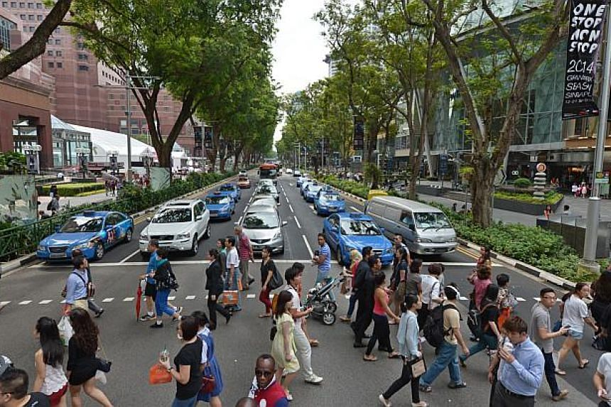 Shoppers crossing at the traffic crossing between Ngee Ann City and Paragon at Orchard Road on Sept 25, 2014. -- PHOTO: ST FILE