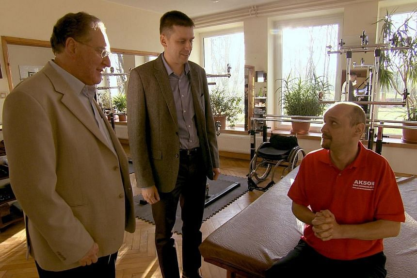In an undated handout picture released by the BBC, Bulgarian man Darek Fidyka (right), who suffered a severed spinal column that rendered him paralysed from the chest down, talks with Polish neurosurgeon Pawel Tabakow (centre) and Geoff Raisman (left